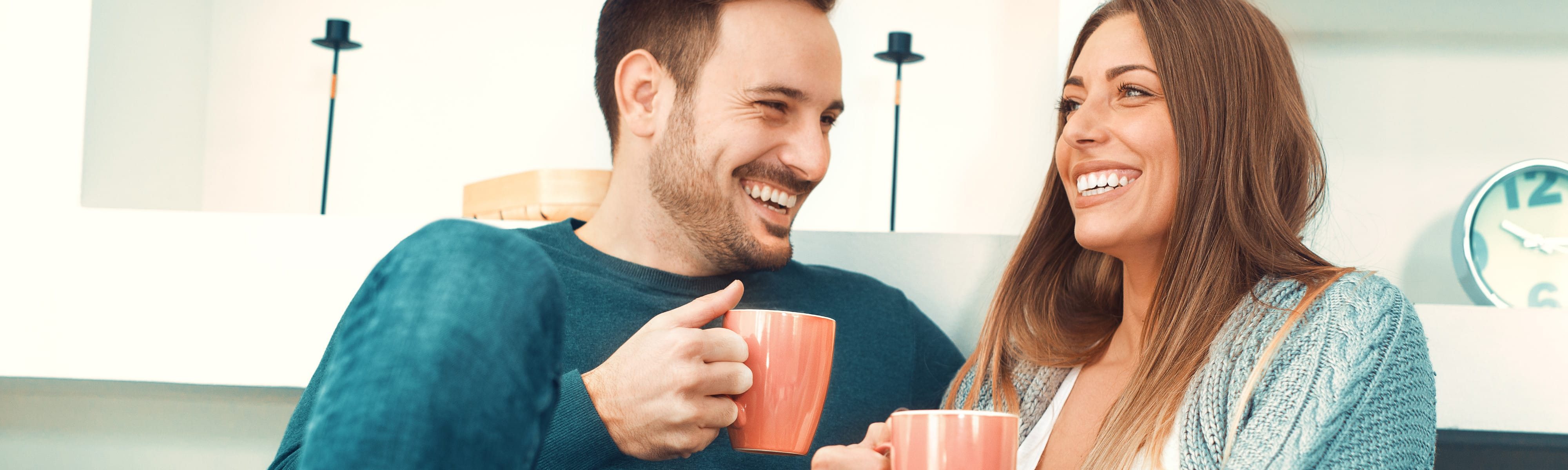 A man and woman drinking coffee on the couch.