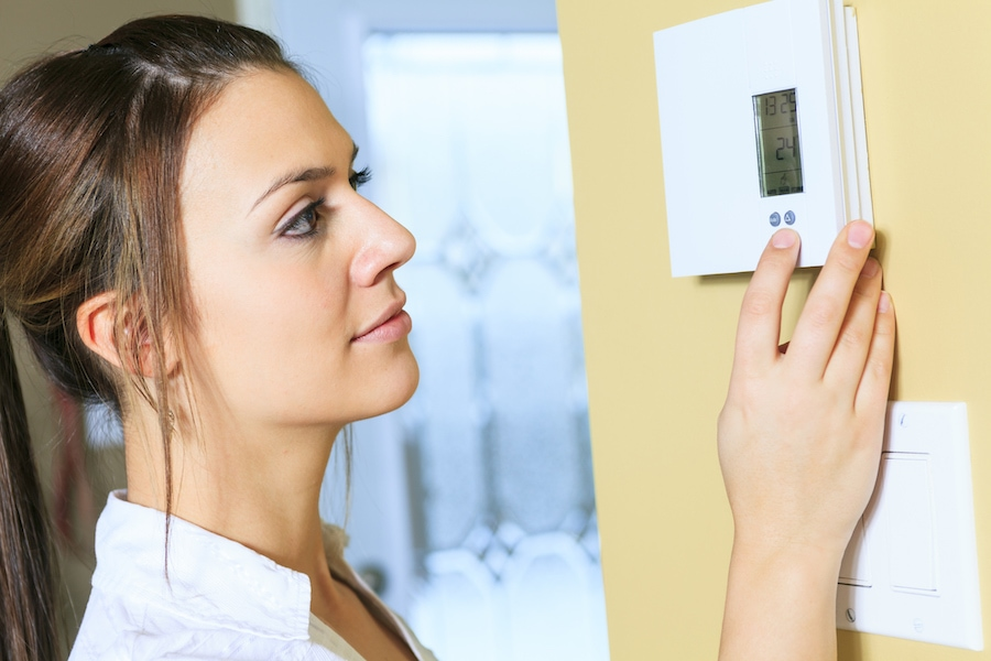 Woman Adjusting Temperature on Thermostat in Her Home
