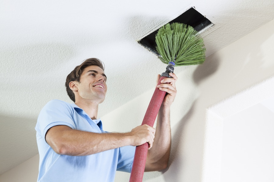Man cleaning air ducts to eliminate mold and dust