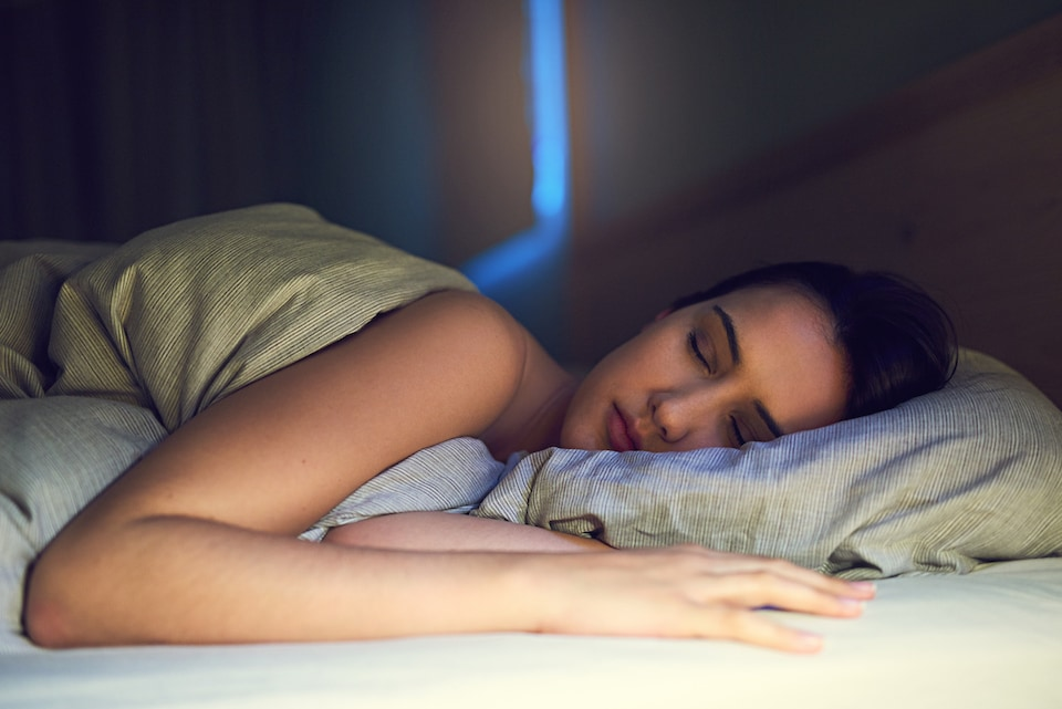 Woman sleeping comfortably due to using her AC while sleeping at night