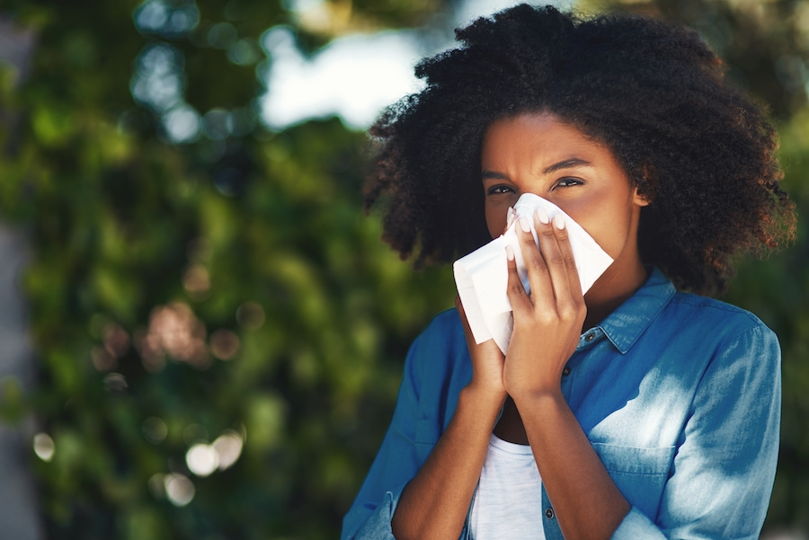 Woman blowing her nose due to seasonal allergies in the springtime