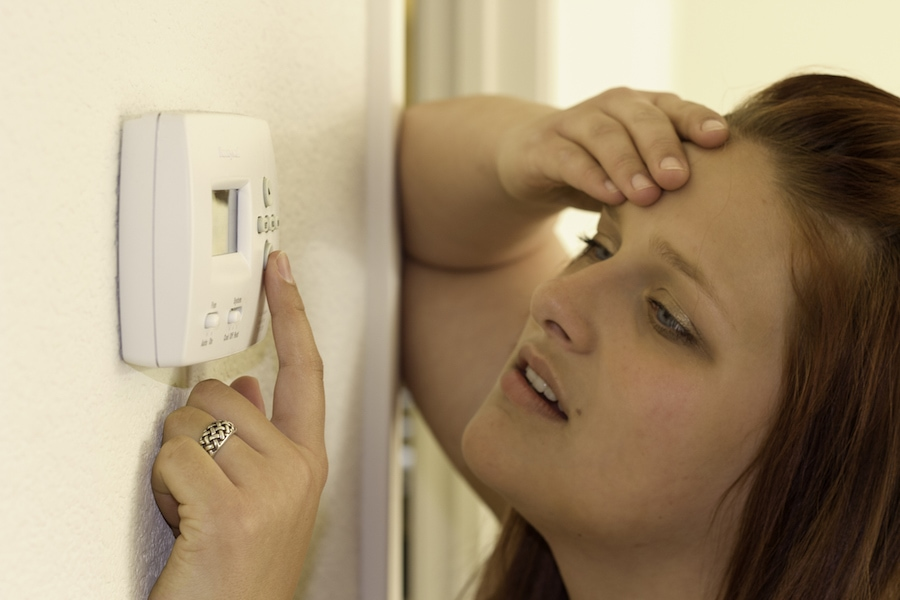 Woman trying to figure out how to troubleshoot her thermostat