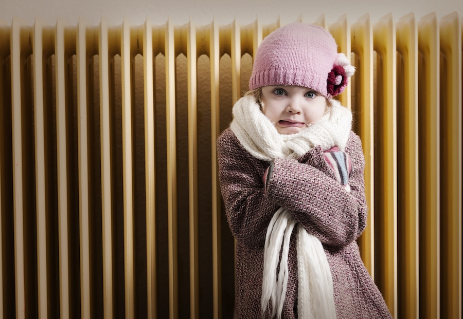 Girl trying to stay warm after realizing her home's furnace is blowing cold air