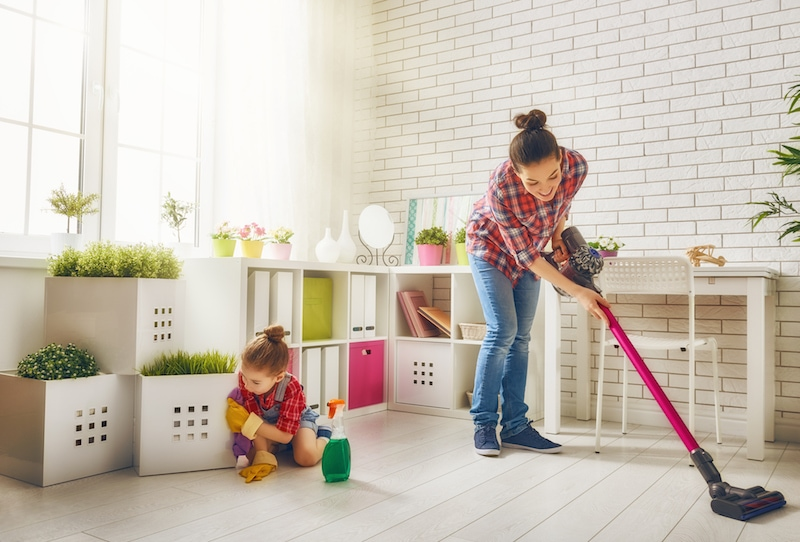 Mother and daughter cleaning the house to help after learning what indoor air quality accessories can help keep their home healthy.