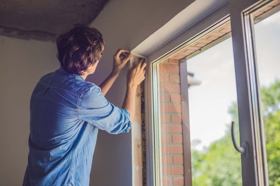 Man checking his window sealing as one of the tips to help with heat gain prevention in his home.