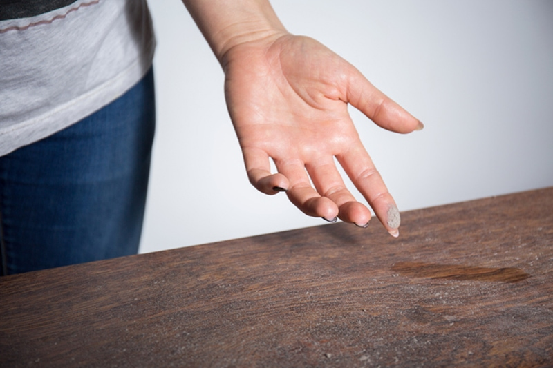 Close-up of dust on woman finger taken from wooden table and wondering how to eliminate it in her home.